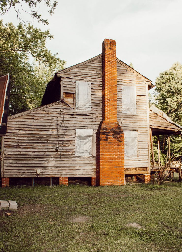 1800's nc farmhouse exterior with weathered wood siding and red brick chimney