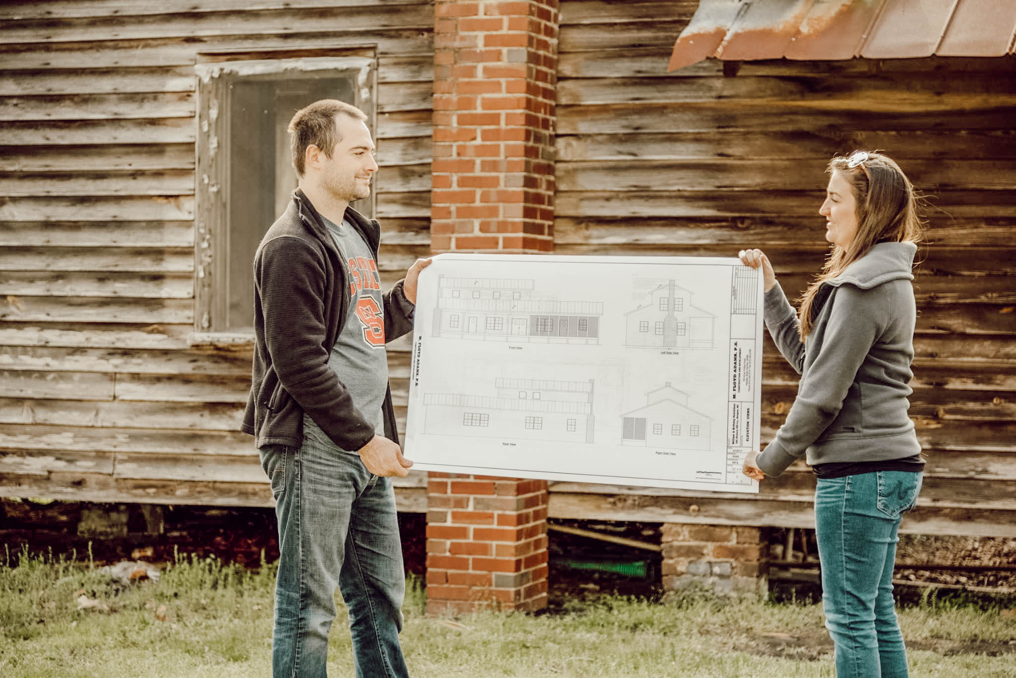 husband and wife holding blueprints by historic farmhouse exterior