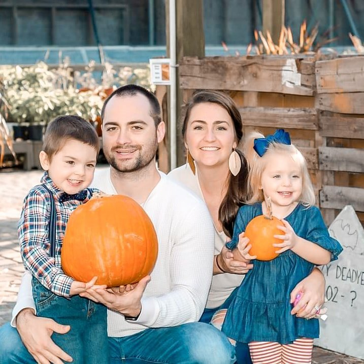 mom, dad, son, and daughter holding pumpkins at a pumpkin patch