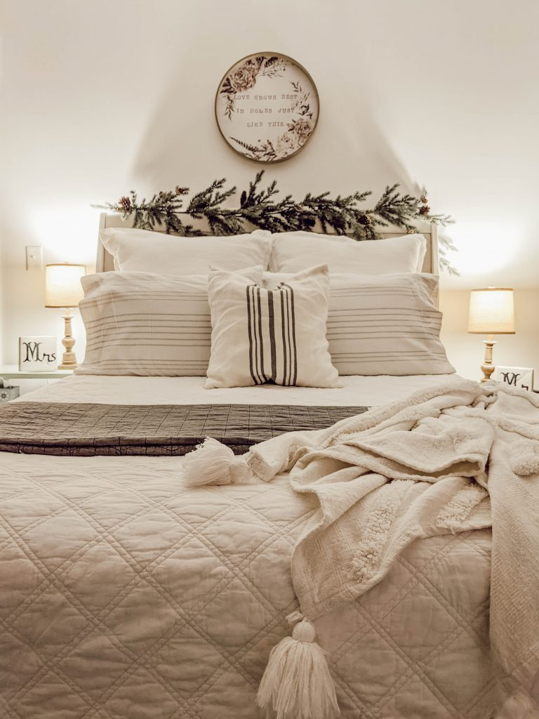 white and gray Christmas bedding with lots of pillows and textured blankets and quilts