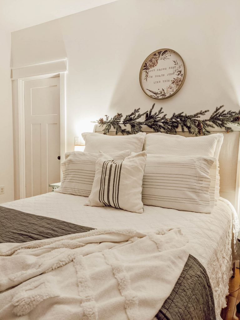 white and gray Christmas bedding with lots of pillows and textured blankets and quilts and garland on the headboard