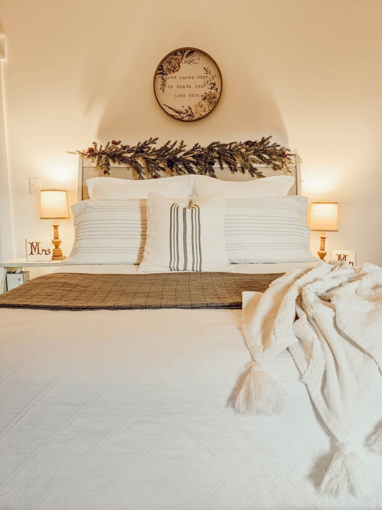 white farmhouse style Christmas bedding and upholstered headboard with garland