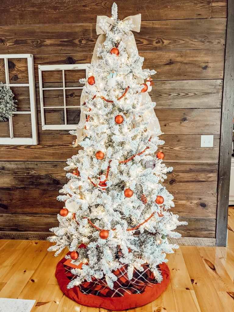 beautiful snowy flocked tree with red  plaid tree skirt and red ornaments