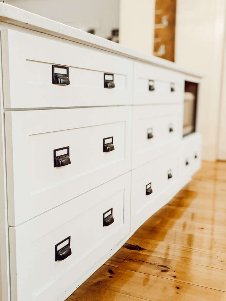kitchen island full of drawers with black hardware